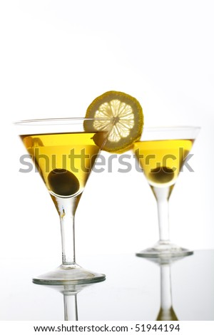 Two glasses with classical martini on reflection surface, garnished olive and lemon.