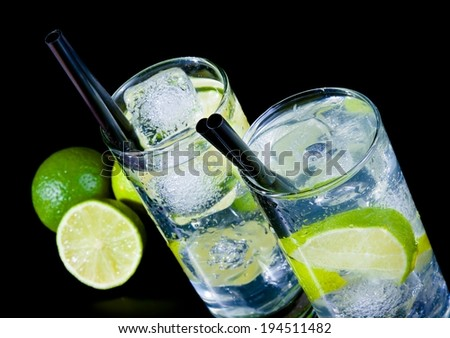 two glasses with cocktail and ice with lime slice on black table, disco club atmosphere - stock photo