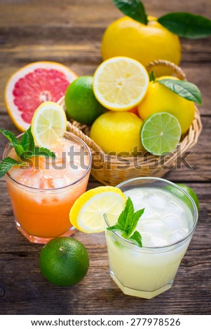 Two glasses with cold lemonade made of lemon and grapefruit - stock photo