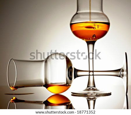 Two glasses with golden colored liquid on a reflective surface - stock photo