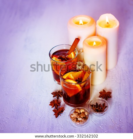 Two Glasses with Mulled Wine, Spices and Candle Light. Selective Focus, Shallow DOF. Square Composition. Christmas Festive Atmosphere. - stock photo