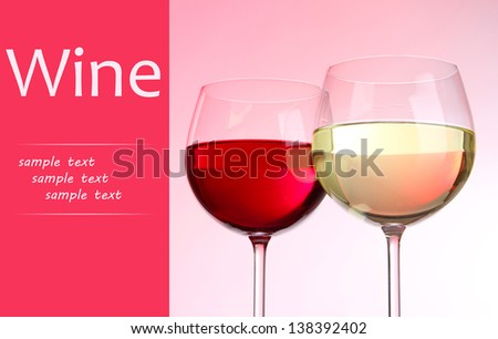 Two glasses with red and white wine on pink background - stock photo