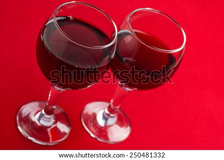 Two glasses with red wine close-up on a red background. - stock photo