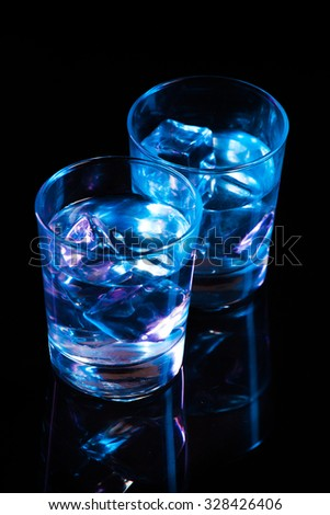 Two glasses with vodka and ice cubes against the background of deep blue glow on  dark mirror - stock photo