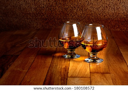 Two goblets of brandy on wooden old counter top  - stock photo