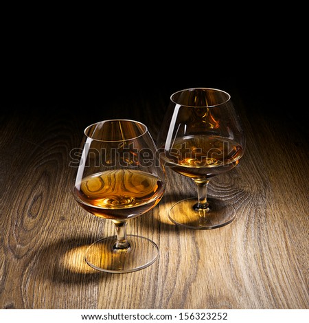 Two goblets of brandy warmed by the glow of the lights on wooden counter top while entertaining a special friend