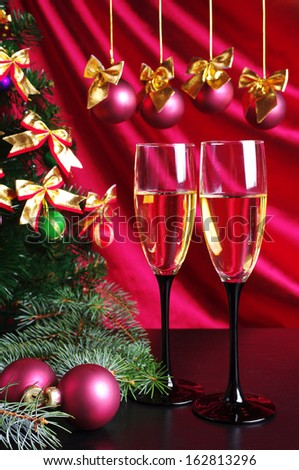 Two goblets of champagne and new year decoration against purple drapery - stock photo