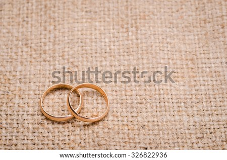 Two gold wedding rings lying on brown cloth sacking - stock photo