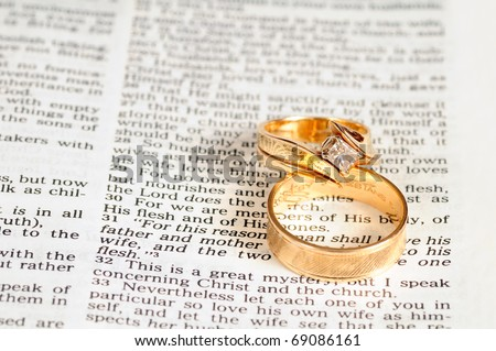 Two gold wedding rings rest on the marriage passage from Ephesians 5 in the Bible - stock photo