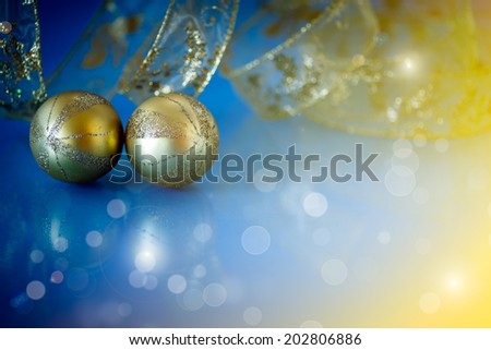 two golden Christmas ball on blurred blue background