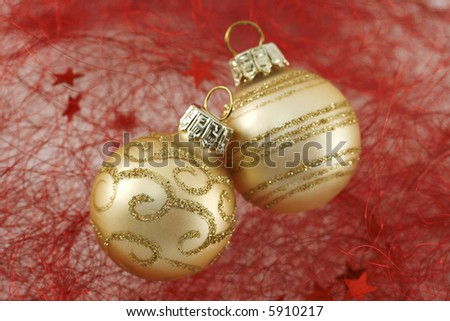 Two golden christmas balls on red