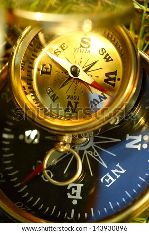 Two golden compasses on green grass
