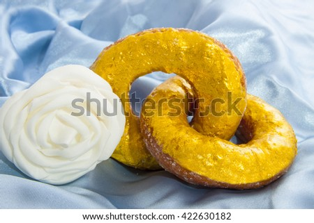 Two golden donuts on blue satin with white rose