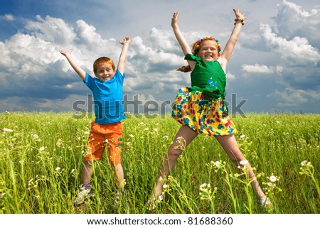 Two golden-haired children play in field - stock photo