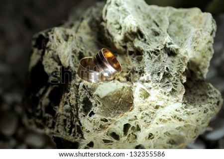 two golden wedding rings on stone - stock photo