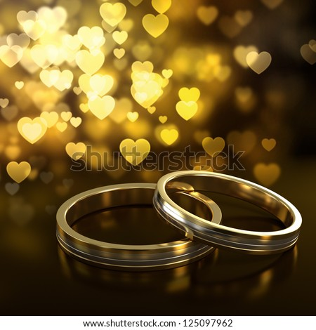 Two golden wedding rings with heart bokeh on background - stock photo
