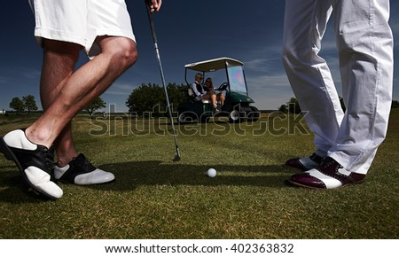 Two golf player on a green field and a golf car.