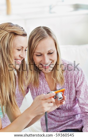 Two gorgeous women using a digital camera at home on a sofa