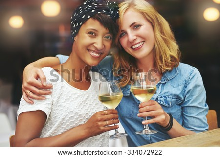 Two gorgeous young multiethnic women enjoying a glass of wine raising their glasses in a toast to the camera as they sit arm in arm in a restaurant