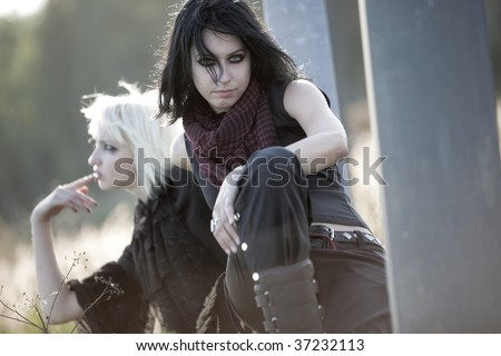 Two goth women concept portrait. Soft sunset light from behind. - stock photo