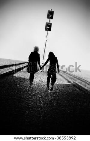 Two goth women walking far on railway. Black and white concept. - stock photo