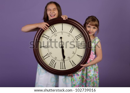 Two grade school kids holding a large wall clock with roman numerals - stock photo