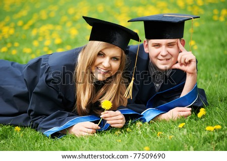 two graduate students guy and girl lying on spring grass smiling
