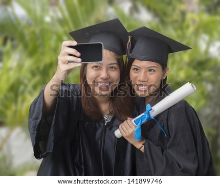 two graduates taking a selfie photo with smart phone - stock photo