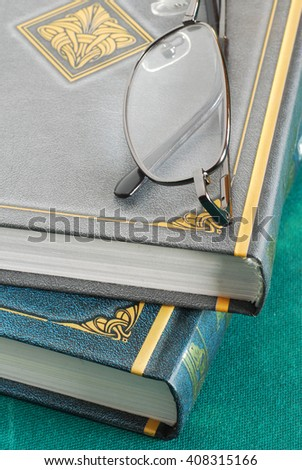 two gray and green books pile with glasses closeup - stock photo