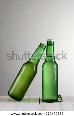 Two green beer bottles on a wood table against a light to dark gray background. One bottle is at a slant leaning on the other bottle. Vertical format with copy space. - stock photo