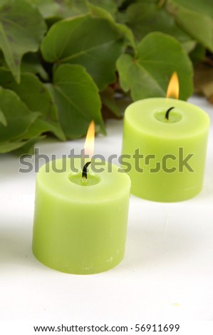 two green burning candle with green ivy