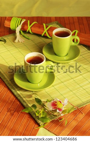 two green cups and saucers, green tea on a bamboo tray - stock photo