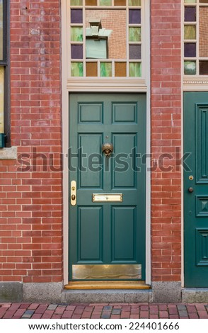 Two Green Front Doors with Colorful Windows Overhead in Brick Building - stock photo
