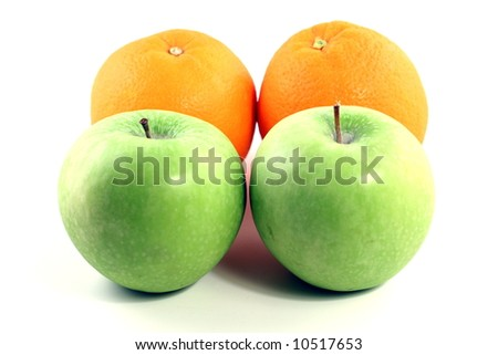 two green granny smith apples and two oranges on a white background