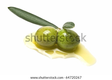 Two green olives on some olive oil and isolated on a white background. - stock photo