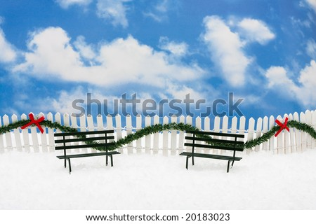 Two green park benches sitting on snow with white fence and green garland on a sky background