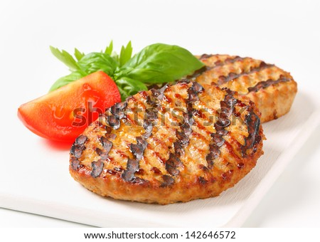 two grilled beef burgers with burned grid - stock photo