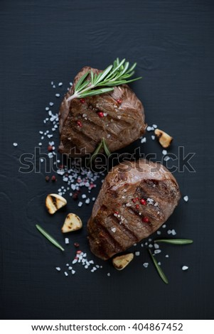 Two grilled beef filet mignon steaks on a black wooden surface, above view