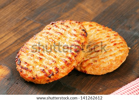 two grilled burgers on a wooden background - stock photo