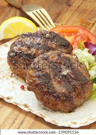two grilled burgers with salad and a pita on a wooden plate