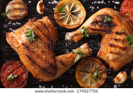 Two grilled chicken legs and vegetables on the grill pan macro. horizontal view from above