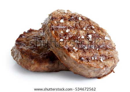 Two grilled hamburger patties with salt isolated on white.