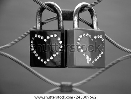 Two grungy love padlocks with heart decoration attached to the bridge in Paris. Valentine's day background. Aged photo. Black and white. - stock photo