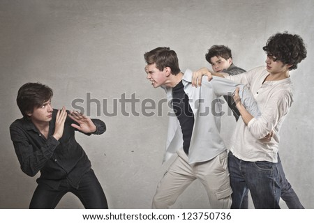 Two guys are quarreling, one of these is held by two friends - stock photo