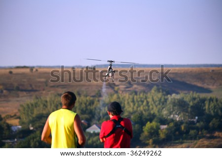 Two guys compete on radio controlled helicopter on nature - stock photo
