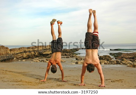 Two guys do handstands at the beach - stock photo