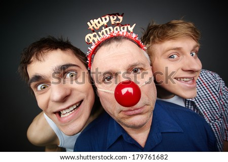 Two guys having fun playing pranks on a senior man celebrating birthday or fool�¢??s day - stock photo