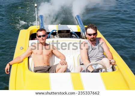 Two guys in a yellow and white speedboat in the sunshine on Lake Coeur d'Alene, ID. - stock photo