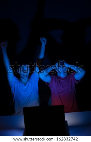 Two guys in front of a computer screen getting all excited about something - stock photo
