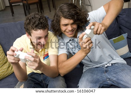 Two guys play video games on a couch - stock photo